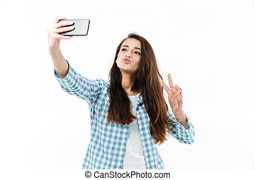 Pretty lovely girl making selfie and showing victory gesture