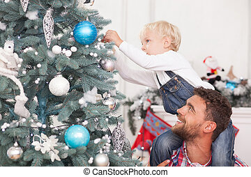 Pretty man and child are decorating New Year tree