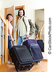 Pretty man and woman together with luggage leaving the home