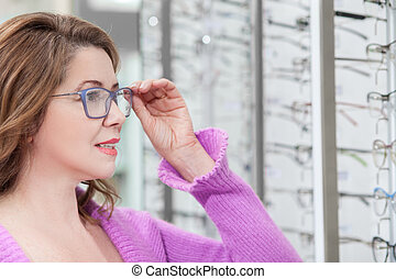 Pretty mature lady is trying on spectacles