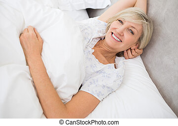 Pretty mature woman resting in bed