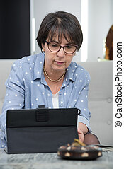 pretty mature woman using tablet computer at home