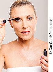 mid age woman putting mascara on her eyelashes