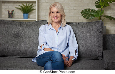 Pretty middle aged woman is sitting on a sofa at home
