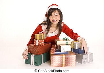 Pretty Miss Santa - A cute asian woman dressed as santa sits...