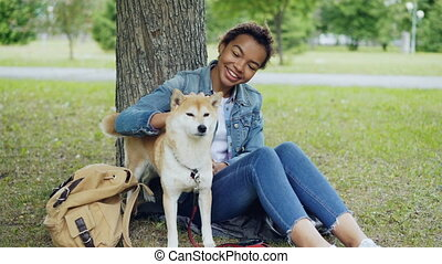 Pretty mixed race girl is petting cute shiba inu dog and...