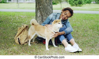 Pretty mixed race woman is fussing her pet dog resting on...