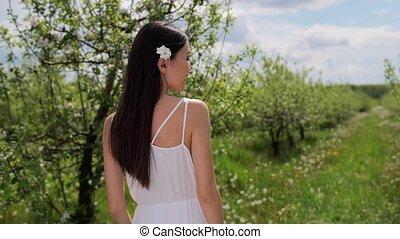 Pretty mixed race woman walking in apple orchard - Rear view...