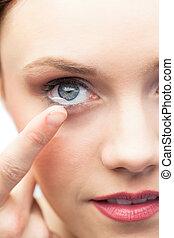 Pretty model applying contact lens