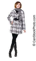 Pretty model in overcoat against white background