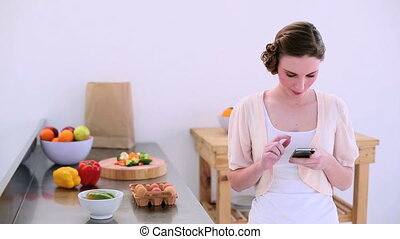 Pretty model texting in kitchen - Pretty model standing in ...