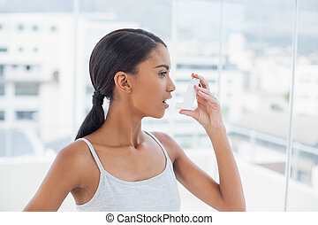 Pretty model using her asthma atomizer