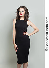 Pretty model woman in black dress posing on white background