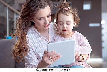 Pretty mom playing tablet with a daughter