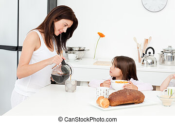 Pretty mom pouring coffee while her children having...