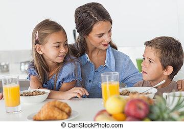Pretty mother having breakfast with her children