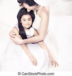 Pretty mother hugging her daughter