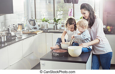 Pretty mother making cake with her beloved children