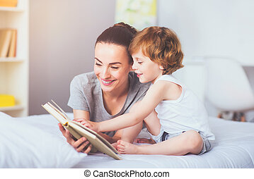 Pretty mother reading a book to her lovely son