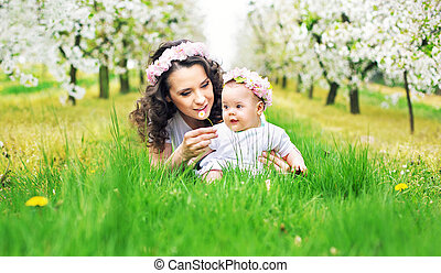 Pretty mother showing her child a dandelion