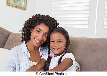 Pretty mother sitting on the couch with her daughter