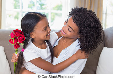 Pretty mother sitting on the couch with her daughter holding roses at home in the living room