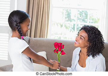 Pretty mother sitting on the couch with her daughter offering roses at home in the living room