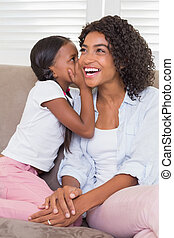 Pretty mother sitting on the couch with her daughter whispering