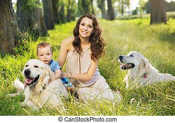 Pretty mother with child and dogs