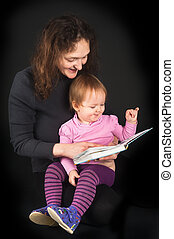 Pretty mother with daughter reading book with tales