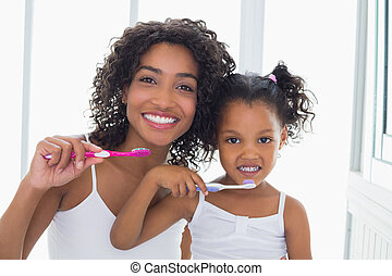 Pretty mother with her daughter brushing their teeth at home...