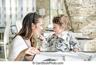 Pretty mother with her little daughter sitting in the restaurant