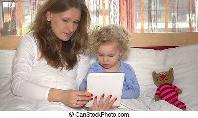 pretty mother with little cute daughter girl playing game on tablet computer