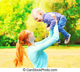 Pretty mother with son child is having fun together outdoors on a summer park