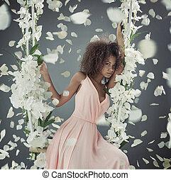 Pretty mulatto woman among white petals - Pretty mulatto...