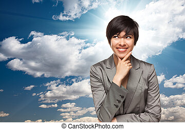 Pretty Multiethnic Young Adult Woman Over Blue Sky and Clouds with Sun Burst Rays.