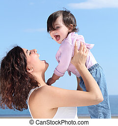 Pretty mum laughing and raising her daughter