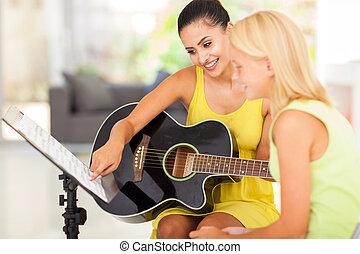 music teacher tutoring young girl to play guitar