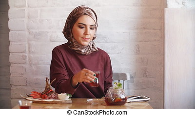 Pretty muslim girl in hijab in cafe. - Pretty muslim girl in...