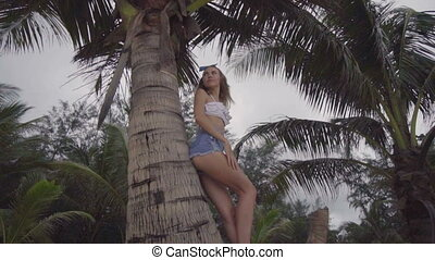 Pretty naturally looking woman on a beautiful summer day between palm trees