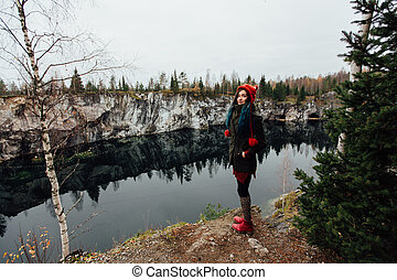 Pretty nice girl enjoy beautiful lake view from the hilltopl and good weather in Karelia. Around the rocks.