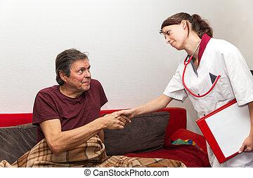 pretty nurse gives senior a hand shake