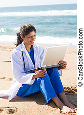 pretty nurse using laptop on beach and smiling