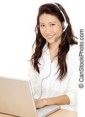 A pretty young asian woman sitting at a desk with laptop computer and headset