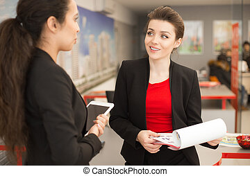 Pretty Office Worker Talking to Colleague