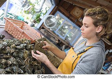 pretty oyster farmer sorting shellfish for sale