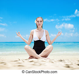 Pretty pale lady meditaitng on a tropical beach