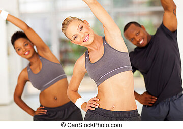 pretty personal trainer exercise with two africans on background