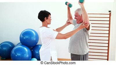 Pretty physiotherapist helping elderly patient lift hand...