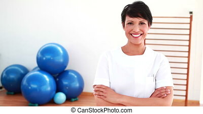 Pretty physiotherapist smiling at camera